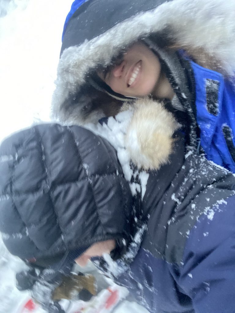 Two humans are dressed in many layers and covered in snow. One human looks downwards so you can't see his face. The other human, wearing a parka, looks at the camera and smiles
