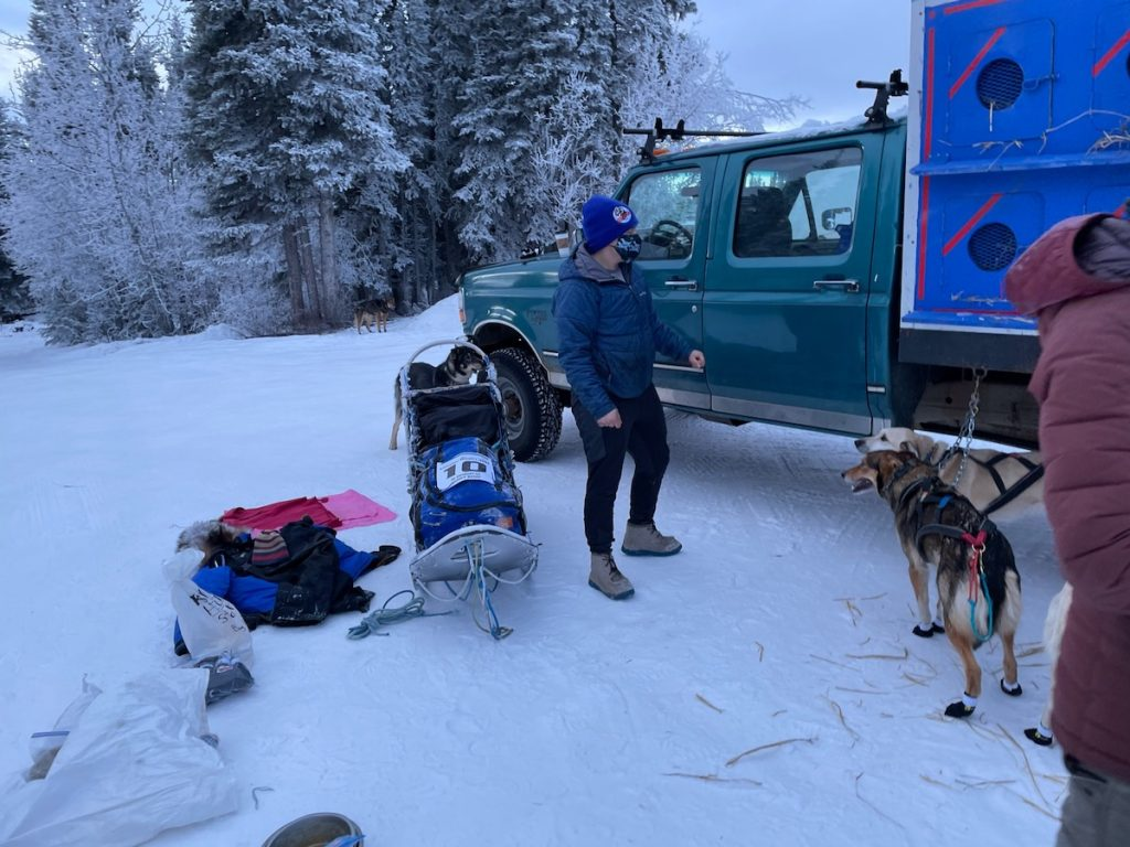 Will stands by the dog truck and his sled. Two dogs in harnesses look at him expenctanly.