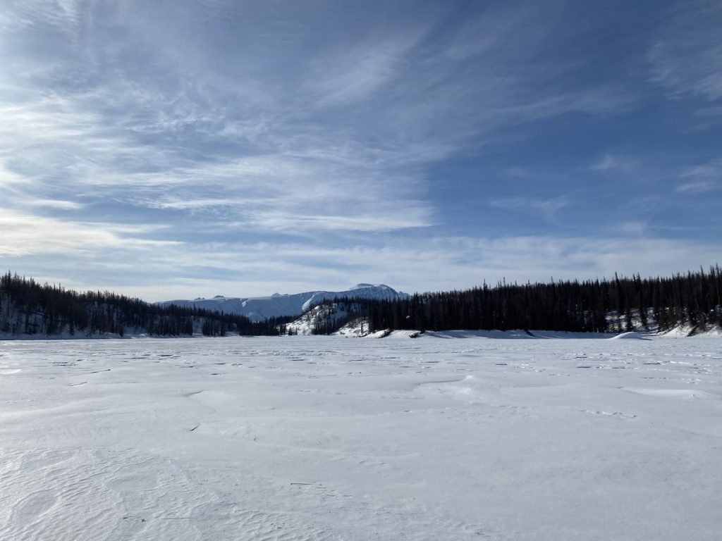 An open snowy lake with ridges of trees on the far side, and a mountain in the background, on a brilliant sunny day
