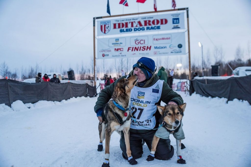 Will kneels with lead dogs Ophelia and Emmy a the finish line of the 2021 Iditarod