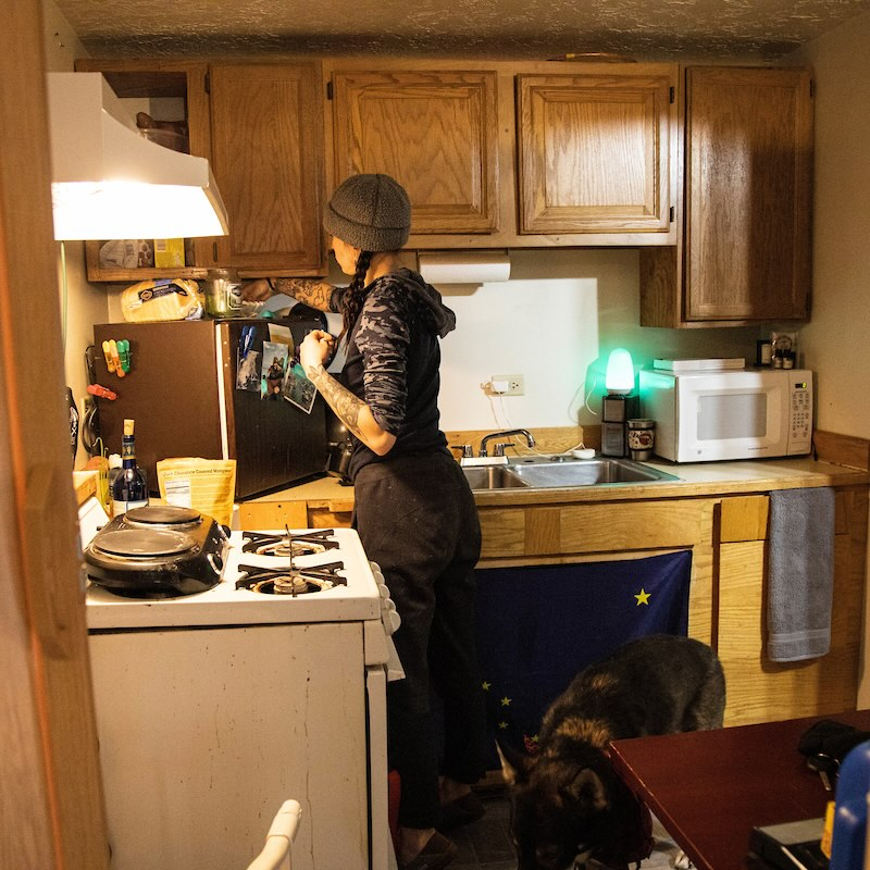 Sam the handler cooks in a tiny kitchen with a small oven, a college-sized small fridge, and cupboards and a microwave in the back