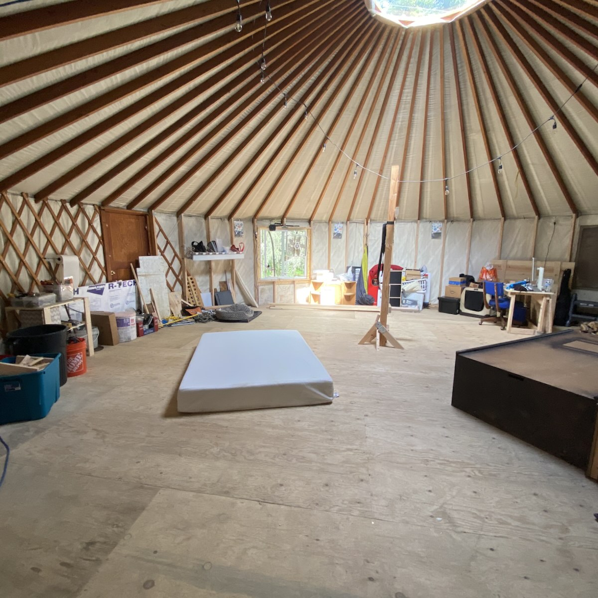 The interior of a large yurt with tools along the wall, a desk in the corner, and a mattress on the floor
